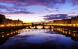 El último tiempo de la puesta del sol en Florencia con las luces de calle se giró y las nubes espectaculares sobre ciudad y el rí Fotos de archivo