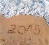 El año 2016 escrito en la arena en un Año Nuevo de la playa está viniendo Imagen de archivo libre de regalías