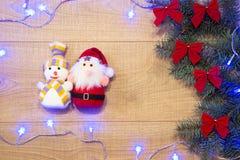 El Año Nuevo/árbol de navidad con los arcos rojos, Papá Noel y el muñeco de nieve juegan, guirnalda azul en la plantilla de mader Imagen de archivo libre de regalías