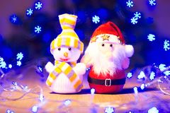 El Año Nuevo/árbol de navidad con los arcos rojos, Papá Noel y el muñeco de nieve juegan, guirnalda azul en la plantilla de mader Imágenes de archivo libres de regalías