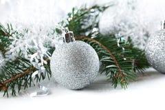 El Año Nuevo, bola de plata de la Navidad con el pino ramifica en el fondo blanco Foto de archivo