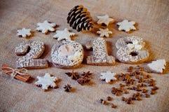 El Año Nuevo de madera numera con diversos decoraions en fondo marrón de la harpillera Imagenes de archivo