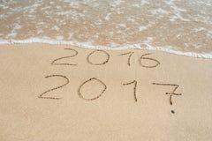 El Año Nuevo 2017 es concepto que viene - la inscripción 2016 y 2017 en una arena de la playa, la onda casi está cubriendo los dí Imagenes de archivo
