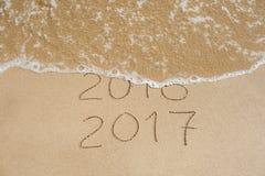 El Año Nuevo 2017 es concepto que viene - la inscripción 2016 y 2017 en una arena de la playa, la onda casi está cubriendo los dí Foto de archivo libre de regalías