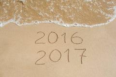 El Año Nuevo 2017 es concepto que viene - la inscripción 2016 y 2017 en una arena de la playa, la onda casi está cubriendo los dí Foto de archivo