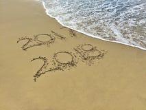 El Año Nuevo 2018 es concepto que viene - la inscripción 2017 y 2018 en una arena de la playa, la onda casi está cubriendo los dí Fotos de archivo libres de regalías
