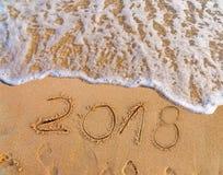 El Año Nuevo escrito en la playa arenosa 2018 está viniendo como concepto del día de fiesta de la fecha Foto de archivo
