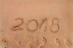 El Año Nuevo escrito en la playa arenosa 2018 está viniendo como concepto del día de fiesta de la fecha Imagen de archivo
