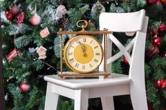 El Año Nuevo está pronto Reloj retro en la silla blanca con el árbol de navidad en fondo Foto de archivo libre de regalías