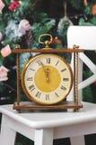El Año Nuevo está pronto Reloj retro en la silla blanca con el árbol de navidad en fondo Fotografía de archivo libre de regalías