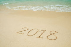 El Año Nuevo 2018 está viniendo 2018 en una arena de la playa, la onda Foto de archivo