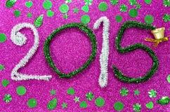 El Año Nuevo figura en base fucsia con la campana Fotografía de archivo