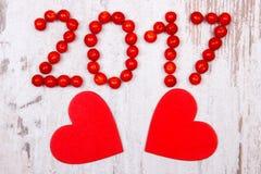 El Año Nuevo 2017 hizo de viburnum rojo y de corazones de madera rojos en viejo fondo de madera Imagen de archivo libre de regalías