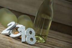 El Año Nuevo número 2018 y las botellas del champán arreglaron en superficie de madera Imagen de archivo