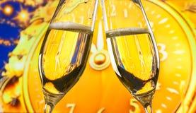 El Año Nuevo o la Navidad en la medianoche con las flautas de champán hace alegrías en fondo de oro del reloj Imagen de archivo libre de regalías