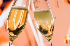 El Año Nuevo o la Navidad en la medianoche con las flautas de champán hace alegrías en fondo del reloj Imagenes de archivo