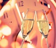 El Año Nuevo o la Navidad en la medianoche con las flautas de champán hace alegrías en fondo del reloj Foto de archivo