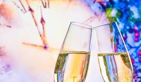 El Año Nuevo o la Navidad en la medianoche con las flautas de champán hace alegrías en fondo del reloj Fotografía de archivo