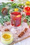 El Año Nuevo reflexionó sobre el vino en un vidrio en el fondo de ramitas, de velas y de guirnaldas Imágenes de archivo libres de regalías
