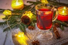 El Año Nuevo reflexionó sobre el vino en un vidrio en el fondo de ramitas, de velas y de guirnaldas Fotografía de archivo