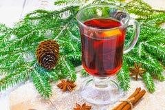El Año Nuevo reflexionó sobre el vino en un vidrio en el fondo de ramitas, de velas y de guirnaldas Fotos de archivo