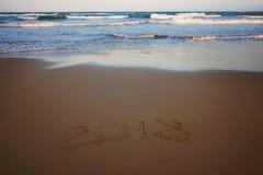 El Año Nuevo 2018 se escribe en la arena en la playa con una onda que hace espuma entrante, horizontal Foto de archivo libre de regalías