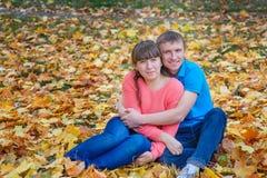 El abarcamiento de los pares jovenes que se sientan en un parque en amarillo se va en aut Imagen de archivo