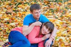 El abarcamiento de los pares jovenes que se sientan en un parque en amarillo se va en aut Fotos de archivo libres de regalías