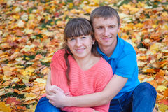 El abarcamiento de los pares jovenes que se sientan en un parque en amarillo se va en aut Imagenes de archivo