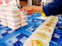 El abastecedor prepara un pedido en bloque un arroz con el plato en polisterin Foto de archivo libre de regalías