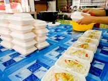 El abastecedor prepara un pedido en bloque un arroz con el plato en polisterin Imágenes de archivo libres de regalías