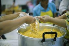 El abastecimiento de la comida a los pobres está ayudando a distribución de seres humanos compañeros junto: Concepto de hambre y  foto de archivo