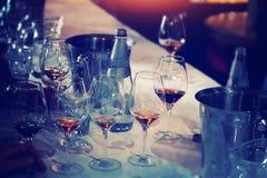 El abastecimiento del degustation del vino mantiene el fondo con los vidrios de vino Fotos de archivo