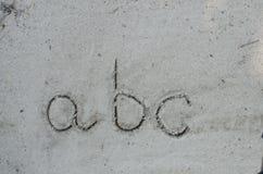 El ABC pone letras a la inscripción en la arena Foto de archivo libre de regalías