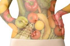 El abdomen de una mujer con las frutas y verduras aisladas en blanco Imagenes de archivo