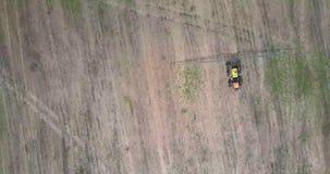 El abejón cuelga sobre el vehículo agrícola en campo cosechado almacen de video