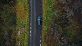 El abejón de la visión superior sigue la conducción de automóviles negra de SUV a lo largo de la carretera en bosque nublado del  almacen de video