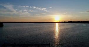 el abejón del lago sunrise 4K vuela al revés entonces aterriza con el muelle y los árboles almacen de metraje de vídeo
