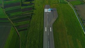 El abejón del tiroteo al avión en la pista da vuelta campo verde en ambos lados almacen de metraje de vídeo