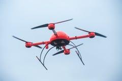 El abejón industrial rojo vuela sobre faci industrial de las estructuras del metal Foto de archivo