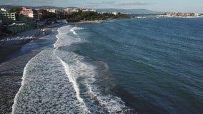 El abejón 4k de la visión aérea tiró de la playa en puesta del sol, ondas del mar se rompe en la playa de la arena almacen de metraje de vídeo
