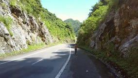 El abejón muestra funcionamientos de la muchacha de la parte trasera a lo largo de la carretera en sombra de la cuesta metrajes