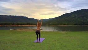 El abejón muestra soportes de la muchacha en actitud de la yoga en la estera contra las colinas