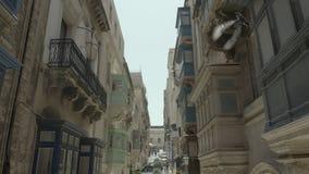 El abejón que vuela adelante, se alza a través de la calle vieja hermosa, La Valeta, Malta Viejo, ventanas del vintage, balcones  metrajes