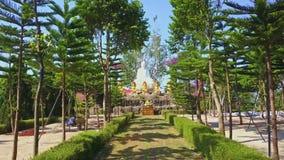 El abejón quita de la estatua de mármol de Buda a través del parque del templo
