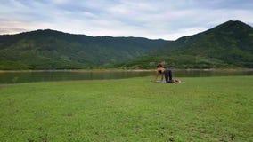 El abejón quita de muchacha en Cat Pose en la pequeña estera por el lago