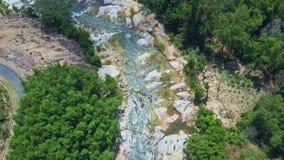 El abejón se mueve a lo largo del río que corre rápidamente entre rocas grandes