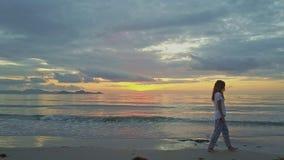 El abejón sigue a la muchacha que va a lo largo de la playa contra salida del sol del mar almacen de video