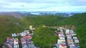 El abejón sube sobre ciudad con la señal en el top de la colina