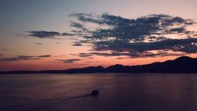 El abejón tiró de una navegación del barco en la puesta del sol almacen de video